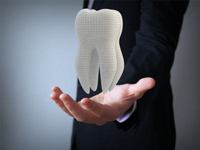 man in suit holding tooth