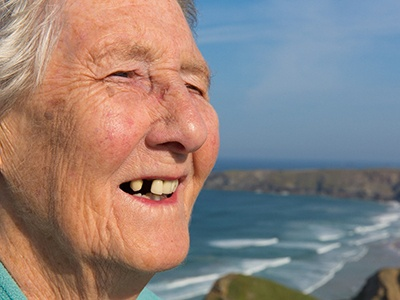 elderly woman smiling needs dental implants in Green Hills