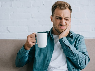 person drinking coffee and holding their jaw in pain