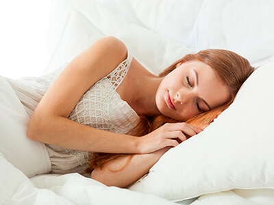 woman sleeping in all white bed