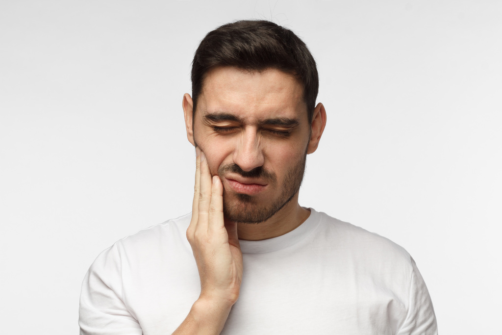 Man in pain considers calling an emergency dentist in Green Hills.