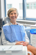 Woman sitting in dentist chair smiling and wearing a dental bib