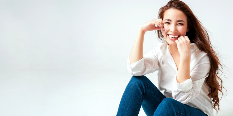 a young woman wearing jeans and a white button-down smiling